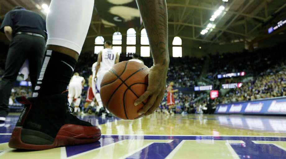 A player picks up the basketball during an NCAA college basketball game between Washington and Washington State, Sunday, March 3, 2013, in Seattle. Photo: Ted S. Warren / Associated Press