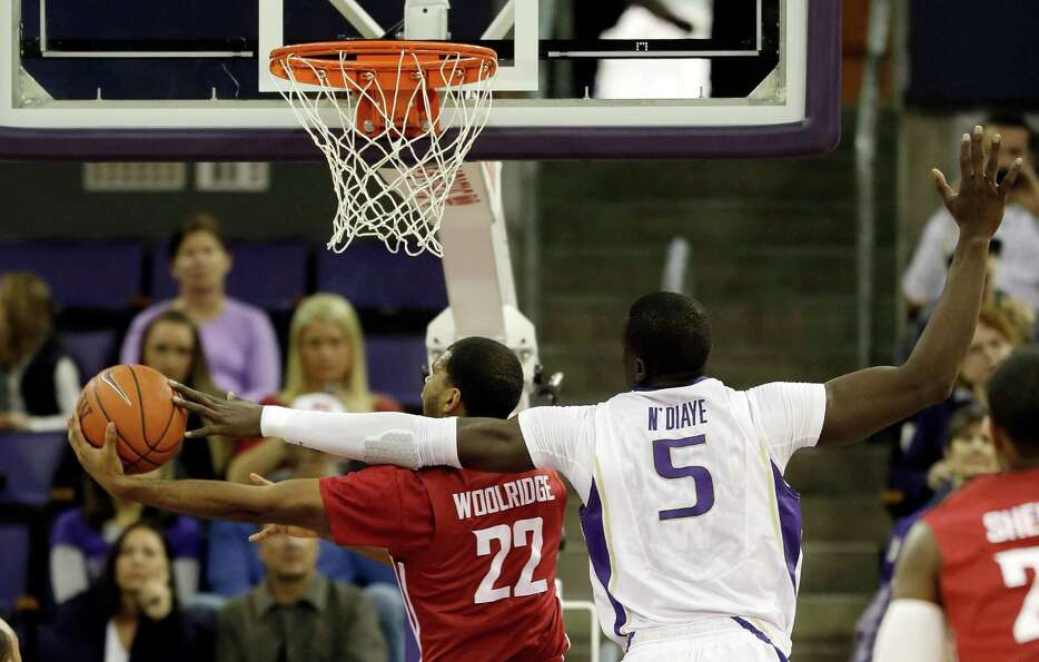 Washington's Aziz N'Diaye (5) tries to block a shot by Washington State's Royce Woolridge (22) in th