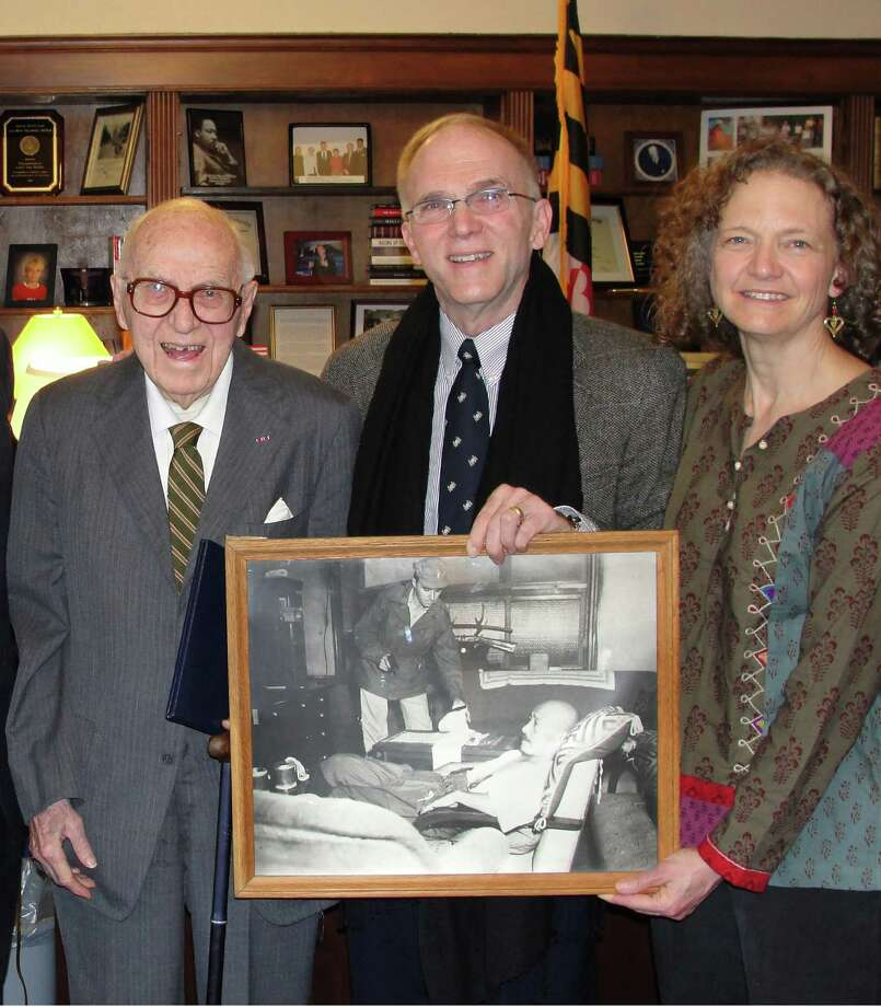 This undated photo provided by the  Office of Congressman Chris Van Hollen, D-Md., shows John J. Wilpers Jr., left,  with his son John J Wilpers III  and daughter Helen Wilpers Read, who are holding a photograph of their father standing over the wounded World War II Japanese leader Hideki Tojo that appeared in publications worldwide. Wilpers Jr. told The Associated Press on Friday, Sept. 10, 2010, that he never wanted all the attention he received when the former Japanese prime minister shot himself in the chest on Sept. 11, 1945. Wilpers was part of a detail sent to Tojo's Tokyo home to arrest him for war crimes. (AP Photo/Office of Congressman Chris Van Hollen, Jimmy Pearson)  **NO SALES** / CONGRESSMAN CHRIS VAN HOLLEN