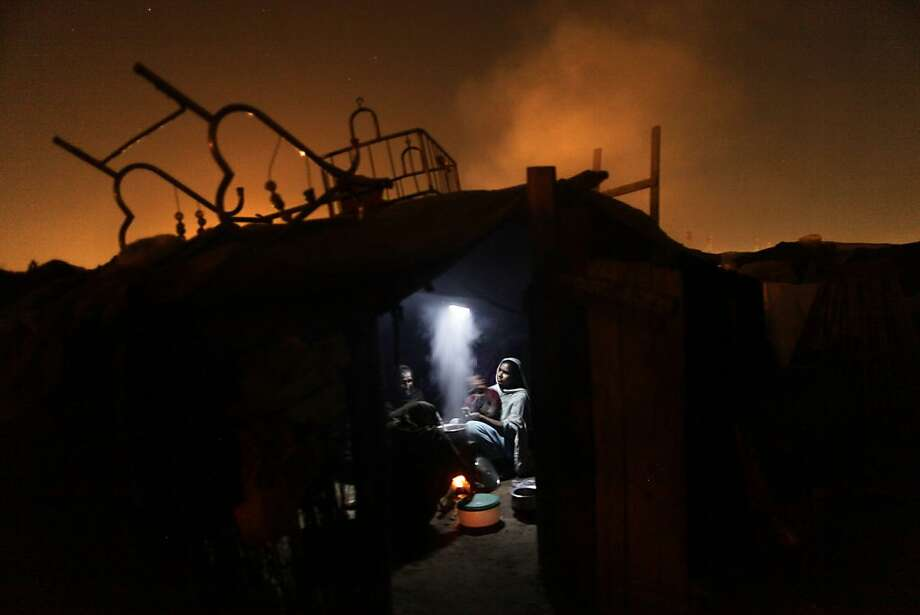 Pakistani women cook for their family using a fire inside their makeshift home, in a slum in Islamabad, Pakistan, Monday, March 4, 2013. Slums which are built on illegal lands have neither running water or sewage disposal.  Photo: Muhammed Muheisen, Associated Press