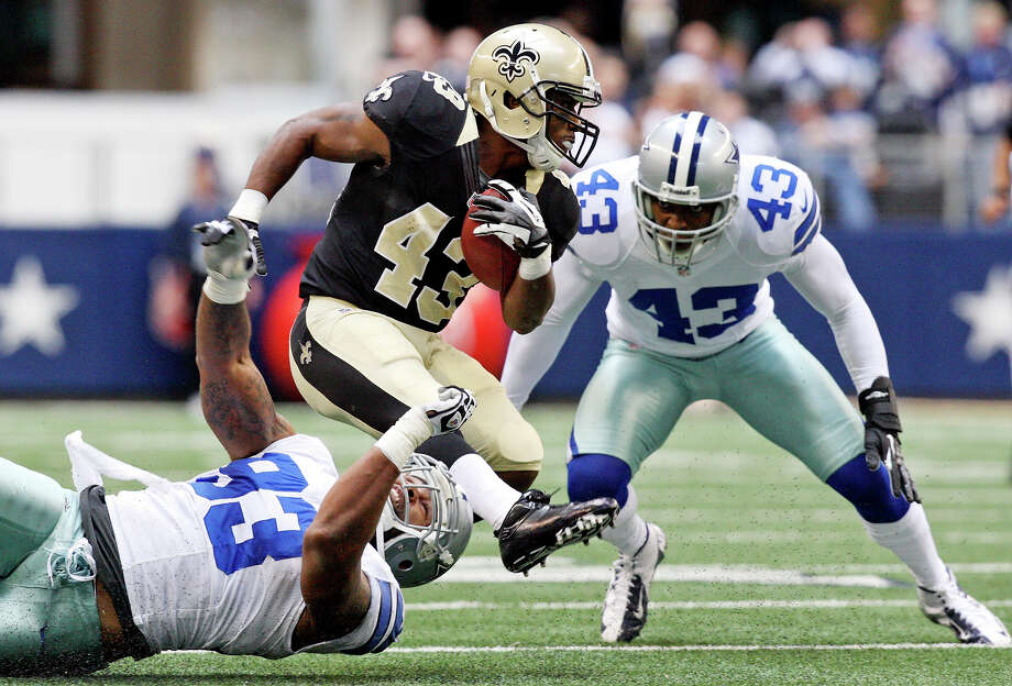 New Orleans Saints' Darren Sproles looks for room between Dallas Cowboys' Anthony Spencer (left) and Dallas Cowboys' Gerald Sensabaugh  during first half action Sunday Dec. 23, 2012 at Cowboys Stadium in Arlington, Tx. Photo: Edward A. Ornelas, San Antonio Express-News / © 2012 San Antonio Express-News