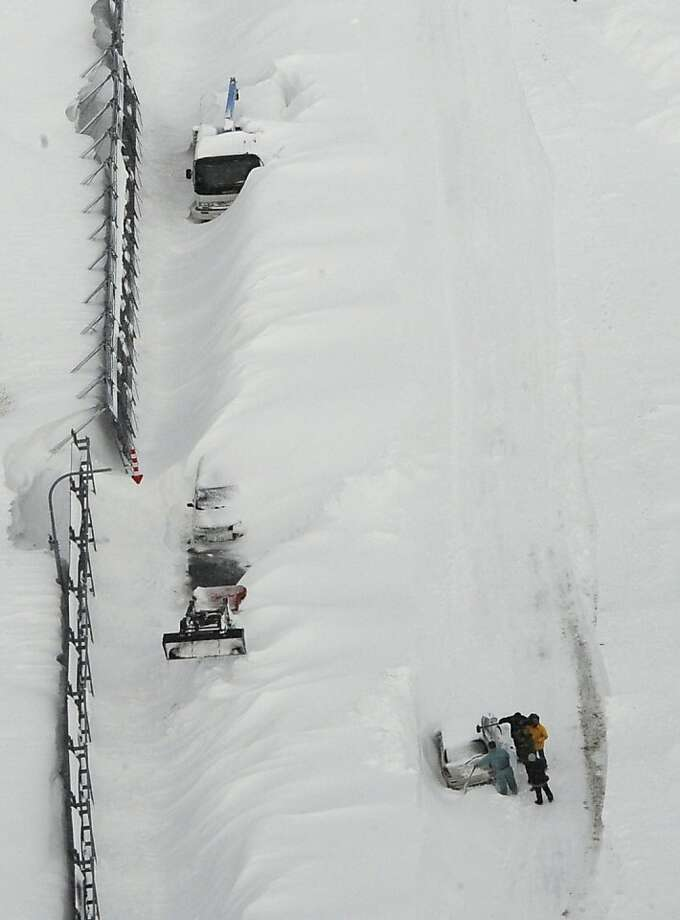 Tragedy in the snow:Stranded vehicles sit buried in drifts along a road in Nakashibetsu, Japan. At least eight people were killed after their vehicles got trapped in heavy snow in Hokkaido prefecture over the weekend. Among the dead were a mother and her three children, who succumbed to carbon-monoxide poisoning. Photo: Associated Press