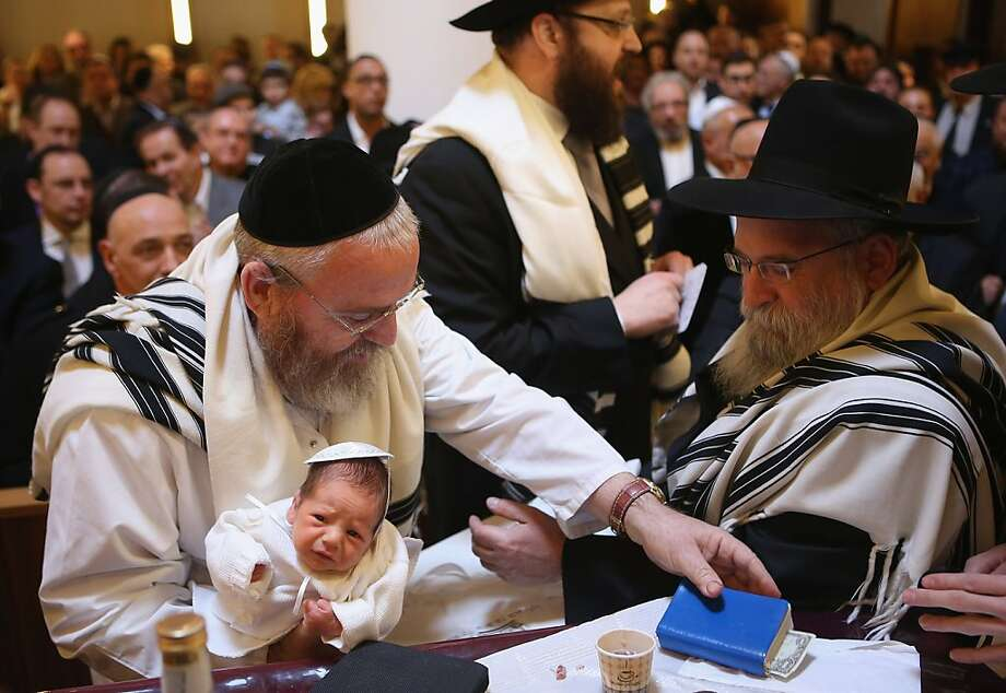 And you thought the sequester cuts were painful:Little Mendl Teichtal wears the dismayed look of the recently circumcised during an orthodox ceremony performed by mohel Manachem Fleischmann (left) at Chabad Lubawitsch synagogue in Berlin. Photo: Sean Gallup, Getty Images
