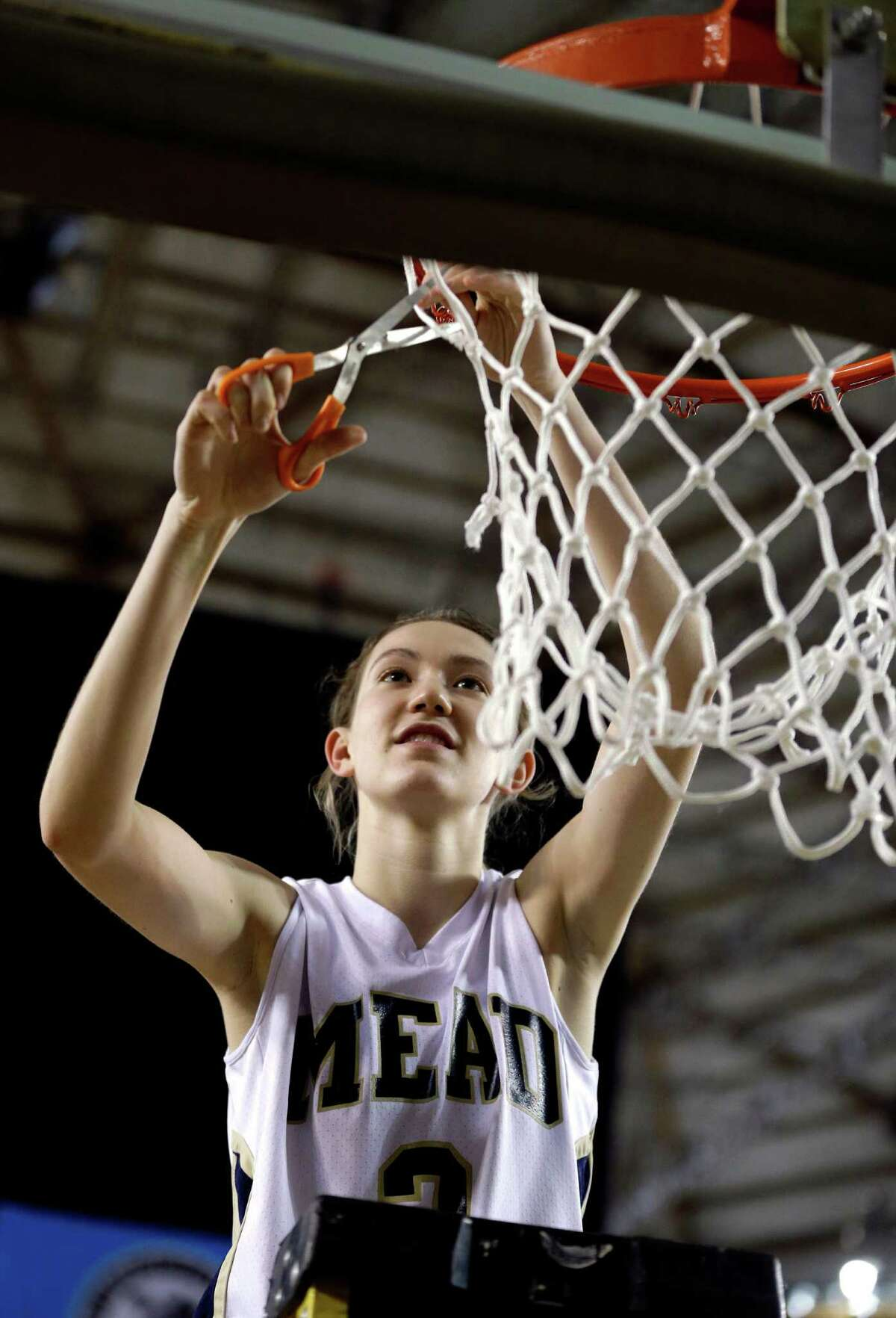 Mead's Sue Winger helps cut down the net after Mead defeated Arlington 58-42 to win the division 4A girls high school basketball championship, Saturday, March 2, 2013, in Tacoma, Wash.