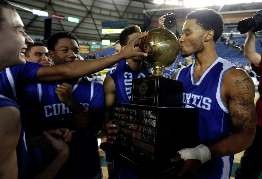 Curtis' Andre Lewis kisses the trophy after the team defeated Jackson 60-56 in the division 4A boys high school basketball championship, Saturday, March 2, 2013, in Tacoma, Wash. Photo: Ted S. Warren / Associated Press