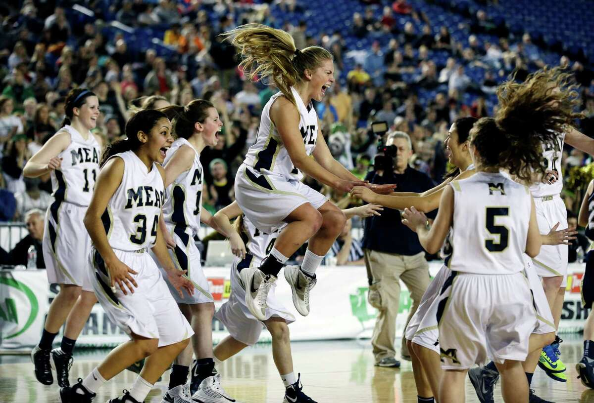 Mead's Morgan Douglass, center, celebrates with her teammates after Mead defeated Arlington 58-42 to win the division 4A girls high school basketball championship, Saturday, March 2, 2013, in Tacoma, Wash.