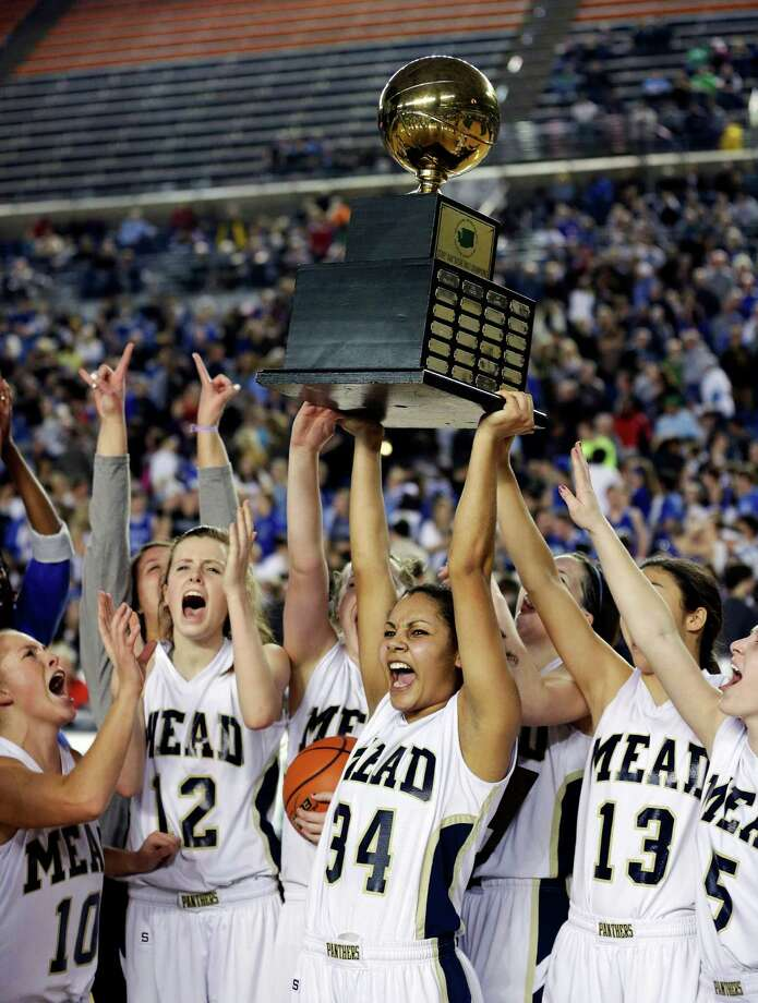 Mead basketball players, including Jade Redmon (34) celebrate with the trophy after they defeated Arlington 58-42 to win the division 4A girls high school basketball championship, Saturday, March 2, 2013, in Tacoma, Wash. Photo: Ted S. Warren / Associated Press
