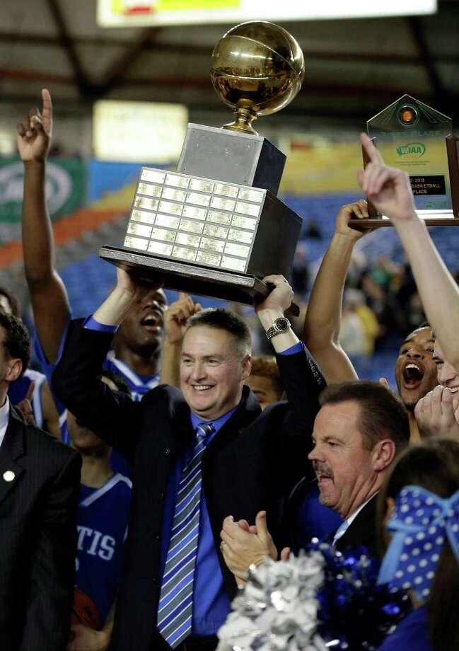 Curtis head coach Tim Kelly holds the trophy as the team celebrates defeating Jackson 60-56 to win the division 4A boys high school basketball championship, Saturday, March 2, 2013, in Tacoma, Wash. Photo: Ted S. Warren / Associated Press