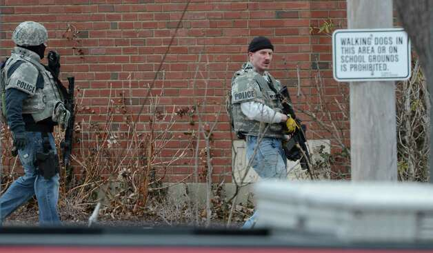 Rensselaer police officers dressed in tactical gear walk around the perimeter of Doane Stuart School March 4, 2013, in Rensselaer, N.Y. after an armed man came to the school.    (Skip Dickstein/Times Union) Photo: SKIP DICKSTEIN