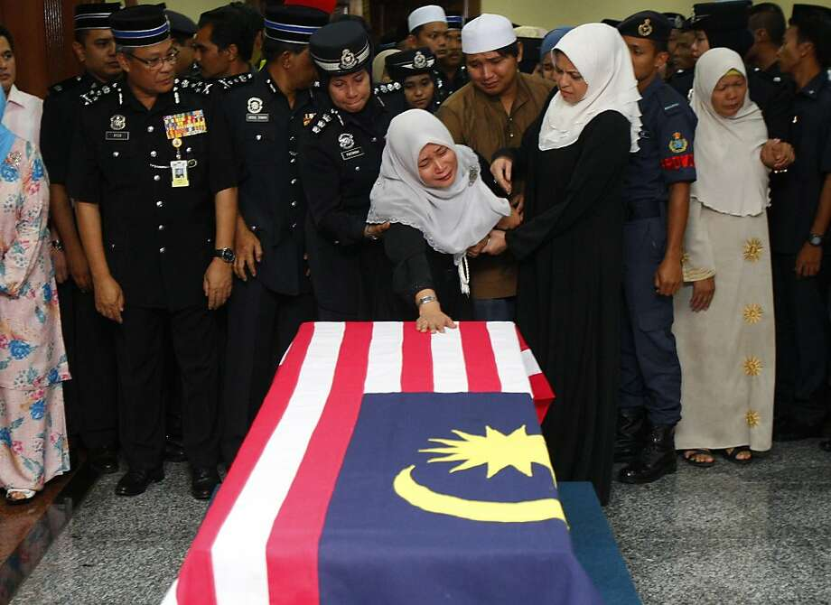 An unidentified family member cries while paying her last respects in front of the coffin of Superintendent Ibrahim Lebar, the Malaysian policeman who was killed in an ambush in Semporna, after its arrival at the Royal Malaysian Air Force base in Subang, near Kuala Lumpur, Malaysia, Monday, March 4, 2013. Malaysia sent hundreds of soldiers to a Borneo state on Monday to help neutralize armed Filipino intruders who have killed eight police officers in the country's bloodiest security emergency in years.  Photo: Lai Seng Sin, Associated Press