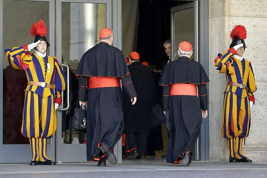 Vatican Swiss guards salute as cardinals arrive for a meeting, at the Vatican, Monday, March 4, 2013. Cardinals from around the world have gathered inside the Vatican for their first round of meetings before the conclave to elect the next pope, amid scandals inside and out of the Vatican and the continued reverberations of Benedict XVI's decision to retire. (AP Photo/Andrew Medichini) Photo: Andrew Medichini, Associated Press