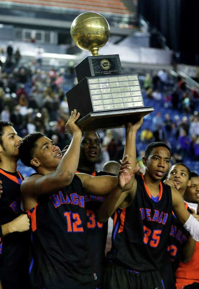 Rainier Beach's Elijah Foster (12) and Shaqquan Aaron (35) lift the trophy for the division 3A boys high school basketball championship, Saturday, March 2, 2013, after Rainier Beach defeated Lakeside 62-59 in overtime in Tacoma, Wash. Photo: Ted S. Warren / Associated Press