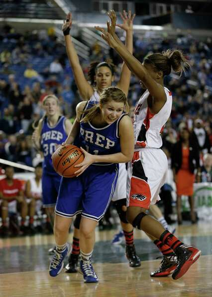 Seattle Prep's Nicole Hall, center, drives around the defense of Cleveland's Webber Donniesha, right