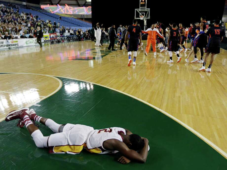 Lakeside's Tramaine Isabell lies on the court as Rainier Beach players celebrate in the background after Rainier Beach defeated Lakeside 62-59 in overtime of the division 3A boys high school basketball championship game, Saturday, March 2, 2013, in Tacoma, Wash. Photo: Ted S. Warren / Associated Press