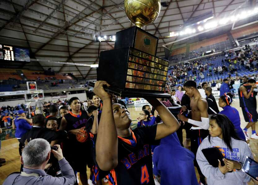 Rainier Beach's Kiewan Miller (4) lifts the trophy for the division 3A boys high school basketball c
