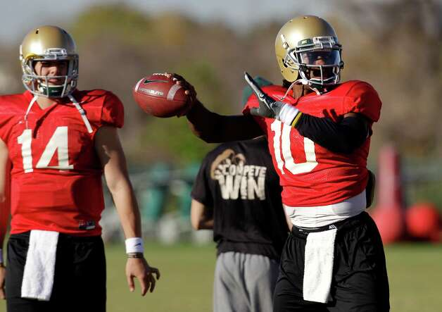 Baylor quarterback Bryce Petty (14) looks on as Robert Griffin III prepares to pass during an NCAA college football practice on  Wednesday, Nov. 30, 2011, in Waco, Texas. Griffin says he is feeling good, with no lingering effects from the concussion-like symptoms that knocked the Heisman Trophy hopeful out of the 19th-ranked Bears' last game. (AP Photo/Tony Gutierrez) Photo: Tony Gutierrez, Associated Press / AP