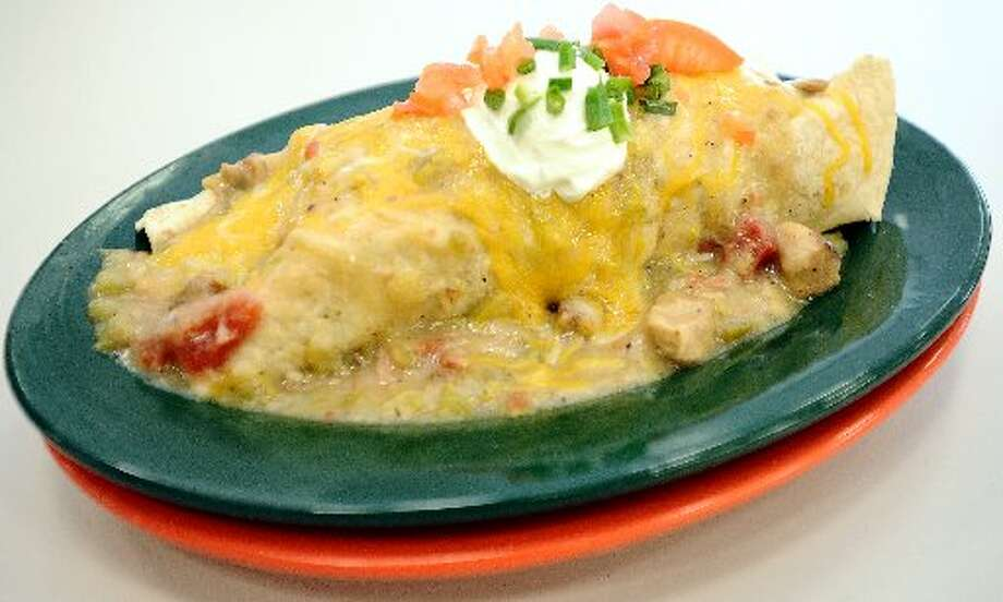 Breakfast Burrito topped with homemade pork green chili, chives, cheese, tomatoes, and sour cream. Randy Edwards/cat5