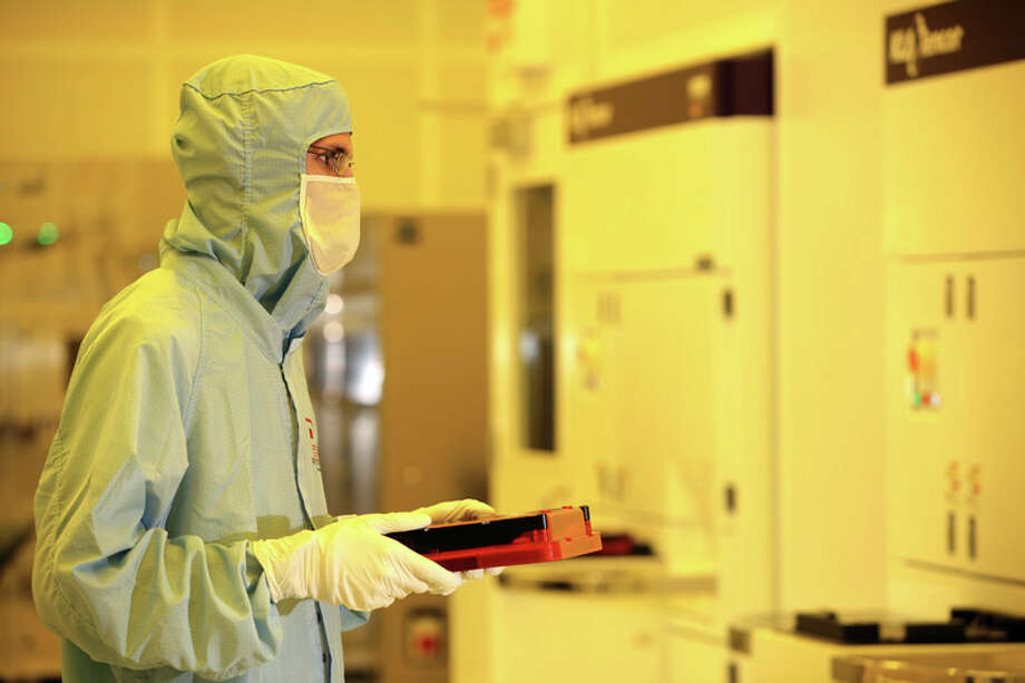 A Photronics worker in one of the companyâÄôs cleanrooms. The Brookfield-based company is completing the purchase of a Taiwanese maker of photomasks. Photo: Contributed Photo / Connecticut Post Contributed