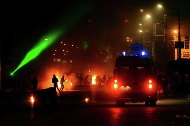 In this Sunday, March 3, 2012 photo, clashes erupt between demonstrators and security forces outside a government building in the Nile Delta city of  Mansoura, Egypt. Protesters in Mansoura and Port Said have been calling for civil disobedience campaigns and work stoppages, to bring down Egyptian President Mohammed Morsi, as violent protests have erupted and activists have accused police of using excessive force in two cities. (AP Photo/Mostafa Darwish) Photo: Mostafa Darwish