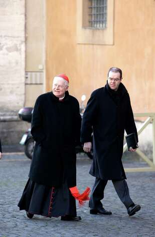 Italian Cardinal Angelo Scola, left, arrives with an unidentified assistant for a meeting, at the Vatican, Monday, March 4, 2013. Cardinals from around the world have gathered inside the Vatican for their first round of meetings before the conclave to elect the next pope, amid scandals inside and out of the Vatican and the continued reverberations of Benedict XVI's decision to retire. (AP Photo/Andrew Medichini) Photo: Andrew Medichini