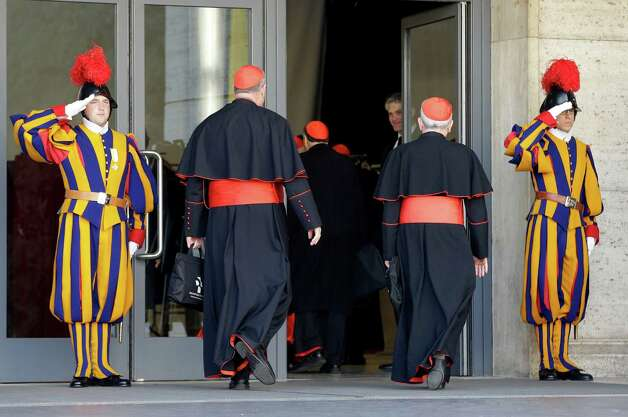 Vatican Swiss guards salute as cardinals arrive for a meeting, at the Vatican, Monday, March 4, 2013. Cardinals from around the world have gathered inside the Vatican for their first round of meetings before the conclave to elect the next pope, amid scandals inside and out of the Vatican and the continued reverberations of Benedict XVI's decision to retire. (AP Photo/Andrew Medichini) Photo: Andrew Medichini