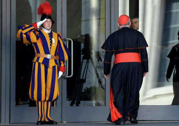 Vatican Swiss guards salute as a cardinal arrives for a meeting, at the Vatican, Monday, March 4, 2013. Cardinals from around the world have gathered inside the Vatican for their first round of meetings before the conclave to elect the next pope, amid scandals inside and out of the Vatican and the continued reverberations of Benedict XVI's decision to retire. (AP Photo/Andrew Medichini) Photo: Andrew Medichini