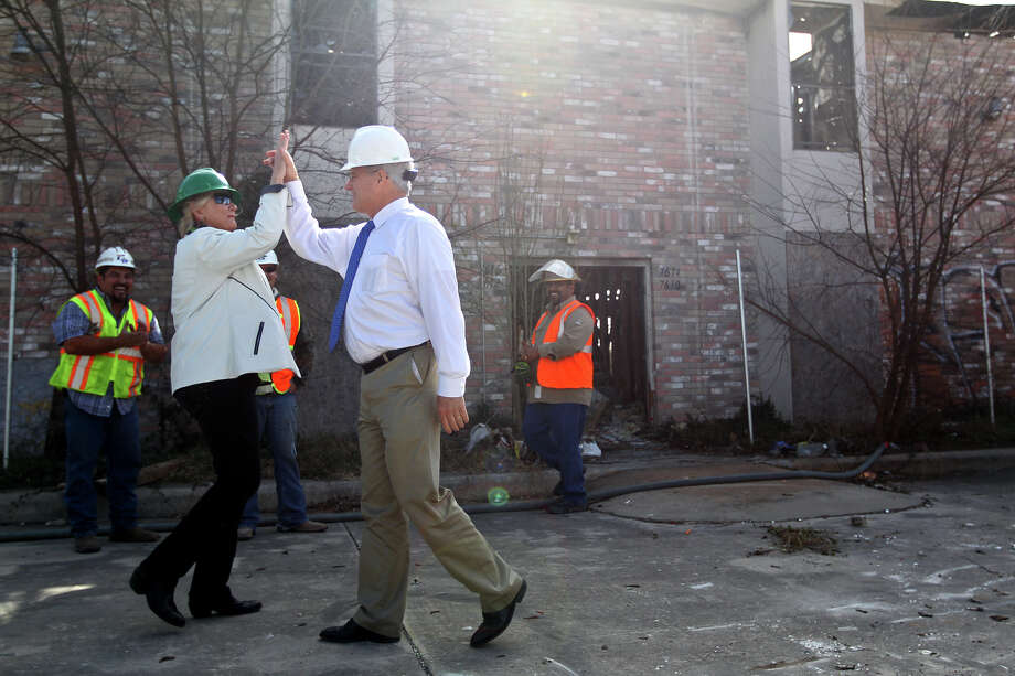 Bexar County District Attorney Susan Reed high fives Pct. 4 County Commissioner Tommy Adkisson at the start of the demolition of two multi-family structures on Windsor Oaks in east Bexar County, Monday, March 4, 2013. It is the latest effort in the ongoing Operation Clean Sweep. The operation was announced in October 2012 and targeted thirty locations mostly in the Camelot II and Windsor Oaks neighborhoods. According to a press release, owners brought 14 properties into compliance. The remaining owners have been charged with criminal violations of health and safety code. Adkisson had the honor of operating a front loader to kick off the demolition. Photo: Jerry Lara, San Antonio Express-News / © 2013 San Antonio Express-News
