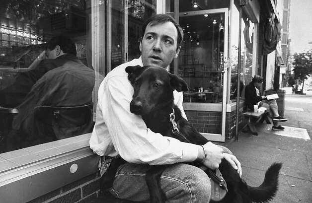 Kevin Spacey holds his black dog while sitting on bench outside a restaurant.  Photo: Ian Cook, Time Life Pictures/Getty Images