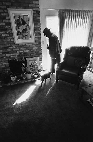 Blues singer John Lee Hooker pausing at the front door as his pet cat tries to follow him out.