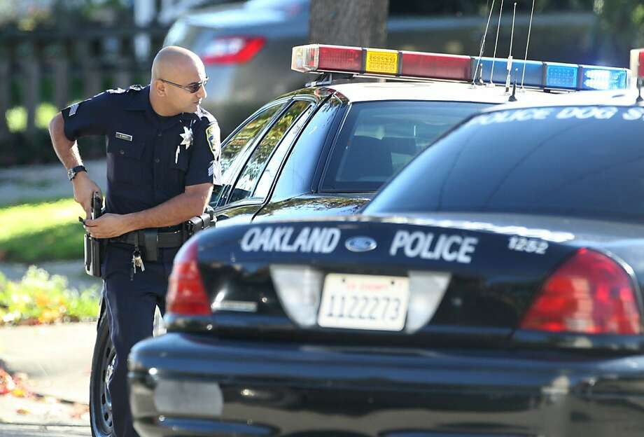 Police officers search an Oakland neighborhood for a suspect in  a home invasion and armed robbery, Monday, Dec. 10, 2012. Photo: Lacy Atkins, The Chronicle