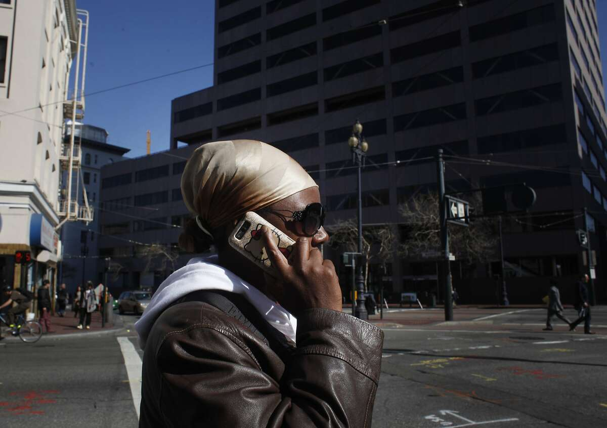 Hoping soon to sign up for a free phone and service plan with a cell phone company called Assurance Wireless, Romonica Grayson, a low income resident of San Francisco who pays $103 a month for a shared phone service with her son, makes a call on Market Street, Monday Mach 04, 2014 in San Francisco, Calif.
