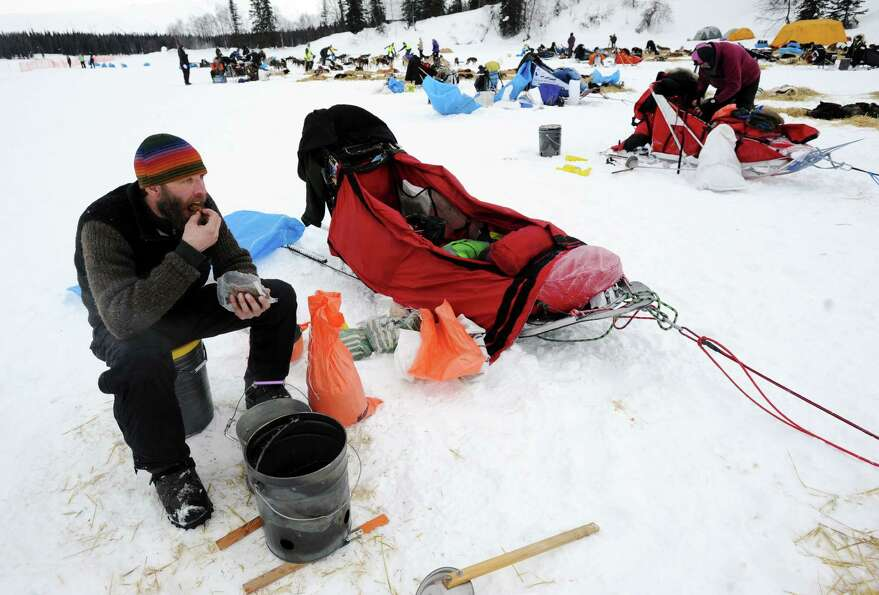 Mike Ellis eats breakfast while resting his dog team at the Finger Lake checkpoint in Alaska during