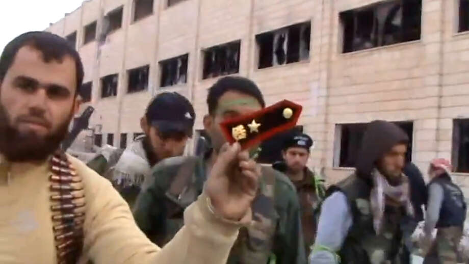 In this Sunday March 3, 2013 image taken from video obtained from the Shaam News Network, which has been authenticated based on its contents and other AP reporting, a Syrian rebel fighters displays an epaulette from a government soldier during a tour of the police academy complex in Khan al-Asal, in the province of Aleppo, Syria. The Britain-based Syrian Observatory for Human Rights said the rebels seized the police academy in Khan al-Asal after entering the sprawling government complex with captured tanks. The Observatory said the battle left at least 120 soldiers and 80 rebels dead. (AP Photo/Shaam News Network via AP video) Photo: Uncredited, HOEP / Shaam News Network