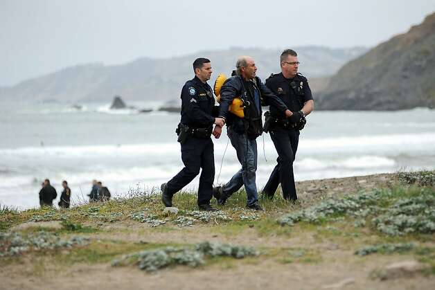 The second male suspect is lead up the beach by police officers after being rescued of the stranded yacht.  An 82 foot sailboat stolen from the Sausalito Yacht Harbor is run aground with suspects  still aboard at Linda Mar Beach in Pacifica, CA Monday March 4th, 2013. Photo: Michael Short, Special To The Chronicle