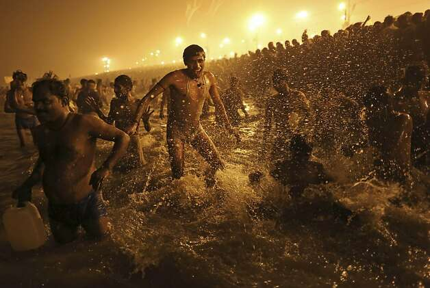 A Hindu man splashes in the water at the confluence of the Ganges and Yamuna rivers and the mythical Saraswati at the Maha Kumbh Mela festival, which draws millions to Allahabad, India. Photo: Kevin Frayer, Associated Press