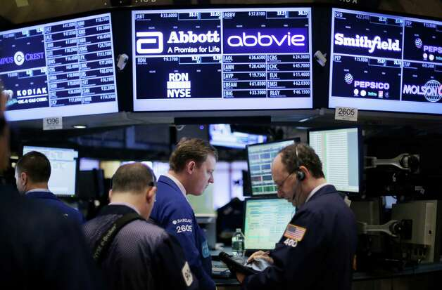 Stock traders work at the New York Stock Exchange, Monday, March 4, 2013 in New York. Uncertainty over the outcome of a budget battle in Washington pushed world stock markets lower on Monday. (AP Photo/Mark Lennihan) Photo: Mark Lennihan