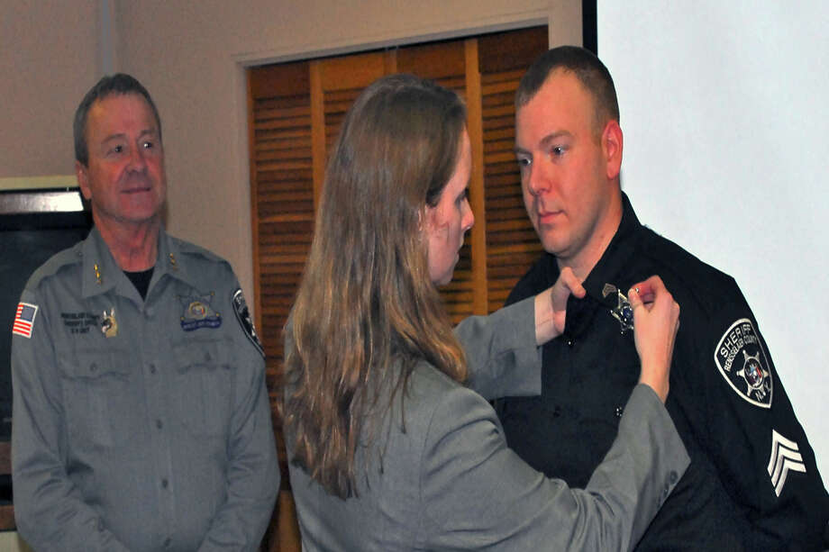 Natalie Gecewicz pins new badge on newly promoted Correctional Sergeant, Justin Gecewicz Friday after being sworn in by Rensselaer County Sheriff, Jack Mahar at the Rensselaer County Public Safety Building. (Submitted by Yvonne Keefe)