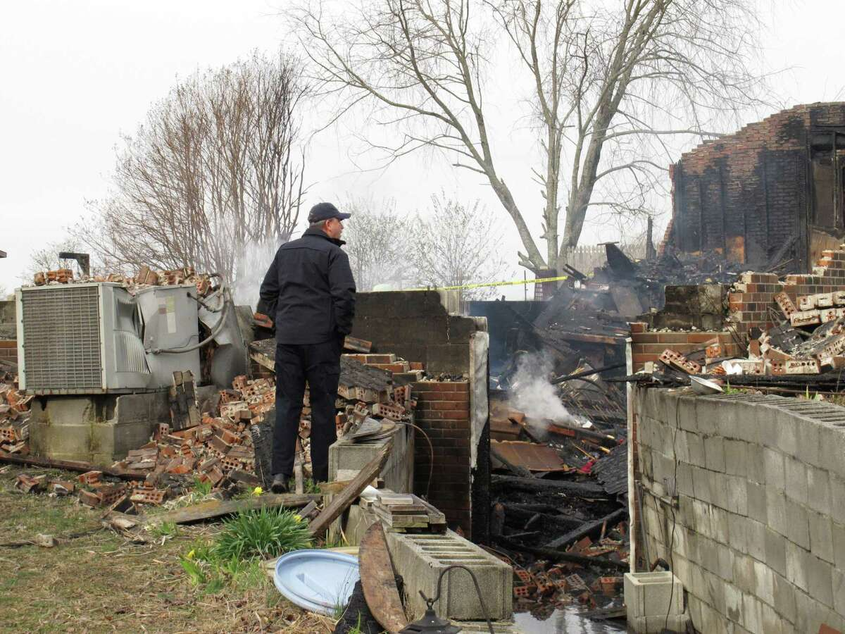 Dewey Woody Jr. of the Tennessee Fire Marshal's Office looks at the ruins of a house in Lafayette, Tenn., where four people died, including three residents and the man who tried to save them.
