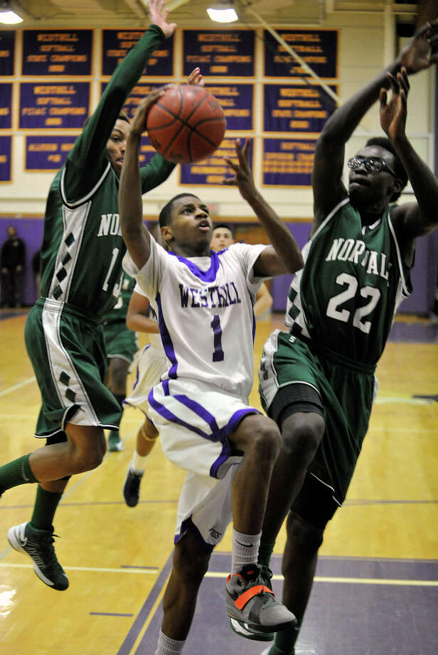 Westhill's Jeremiah Livingston shoots while under pressure from Norwalk's Jeremy Linton, left, and Roy Kane during their game at Westhill High School on Monday, March 4, 2013. Westhill won, 60-50. Photo: Jason Rearick / The Advocate