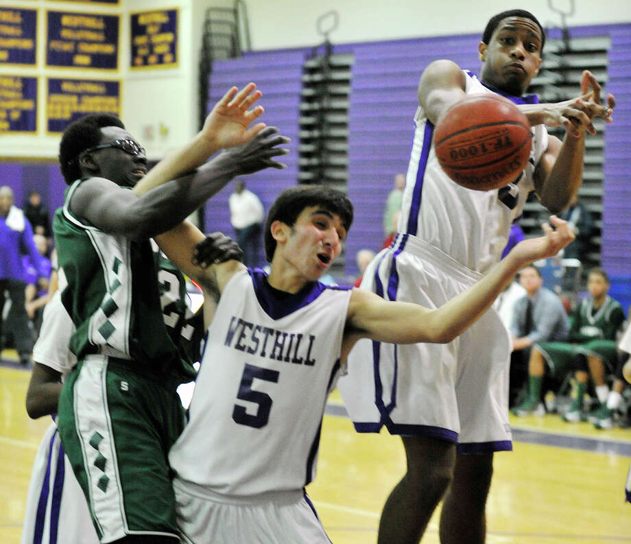 Norwalk's Roy Kane and Westhill's Evan Skoparantzas, center, and Ariel DelaCruz compete for the loose ball during their game at Westhill High School on Monday, March 4, 2013. Westhill won, 60-50. Photo: Jason Rearick / The Advocate