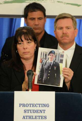 Leanne Sparling holds up a photo of her son Pvt. Michael Sparling who died in a DMAA-related incident as former major league baseball player Jose Canseco, left rear looks on during a press conference at the Capitol March 4, 2013 on the dangers of the drug DMAA and other performance enhancing drugs  (Skip Dickstein/Times Union) Photo: SKIP DICKSTEIN