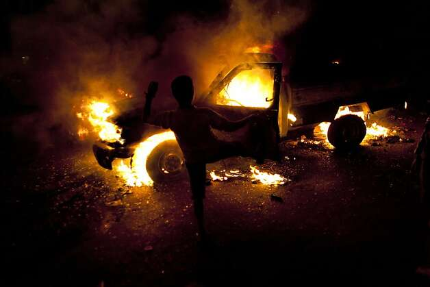 A protester kicks an Egyptian police pickup truck that was set on fire by anti-president Mohammed Morsi protesters on the 6th of October bridge, in Cairo, Egypt, Monday, March 4, 2013. In at least two separate incidents in Cairo on Monday, protesters torched two police vehicles, setting them on fire and driving the policemen in the cars running in the middle of traffic on major thoroughfares.  Photo: Nasser Nasser, Associated Press