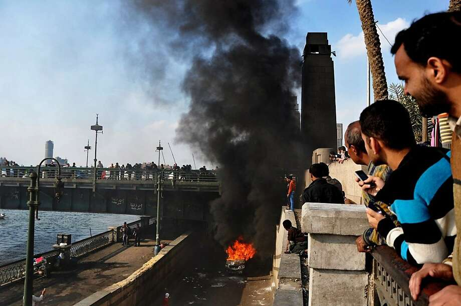 Smoke rises from a police vehicle that protesters set on fire, under Qasr El-Nile Bridge leading to Tahrir Square, Cairo, Egypt, Monday, March 4, 2013.  Photo: Hussein Tallal, Associated Press