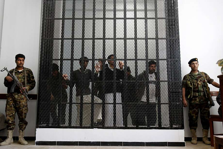 Yemeni soldiers stand guard as suspected al-Qaida militants, behind bars, attend their first hearing in a state security court in Sanaa, Yemen, Monday, March, 4, 2013.  Photo: Hani Mohammed, Associated Press