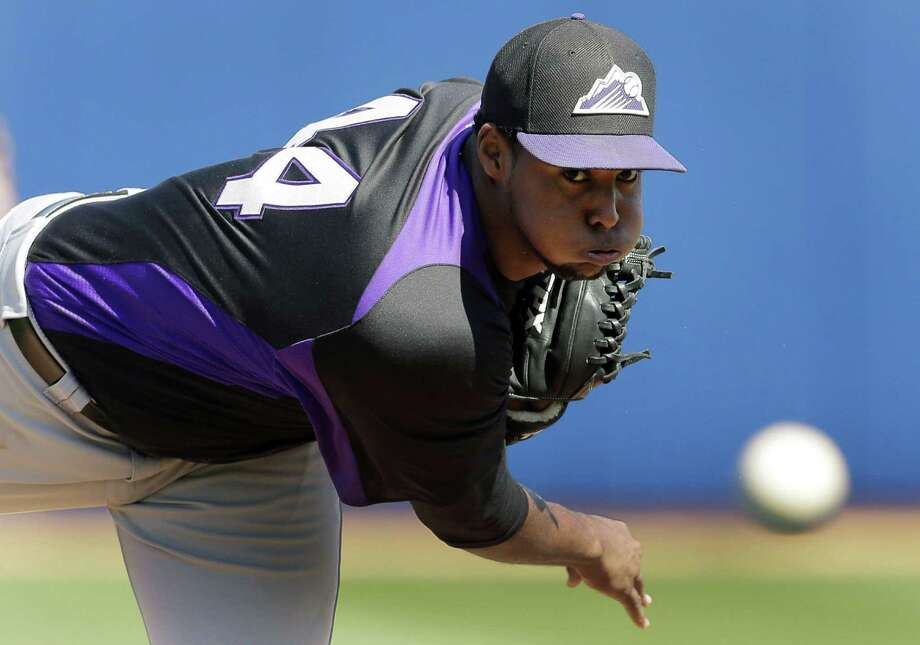 Rockies pitcher Juan Nicasio delivers a first-inning pitch during Colorado's 16-6 loss to Seattle. Photo: Charlie Riedel / Associated Press