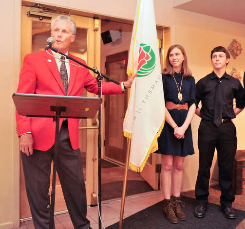 Tournament of Roses President R. Scott Jenkins presents the Tournament of Roses flag to Johnson High School senior band members Carrigan Miller and Austin Irle. The band was among 20 bands invited to march in the 125th Rose Parade on Jan. 1. Photo: Robin Jerstad