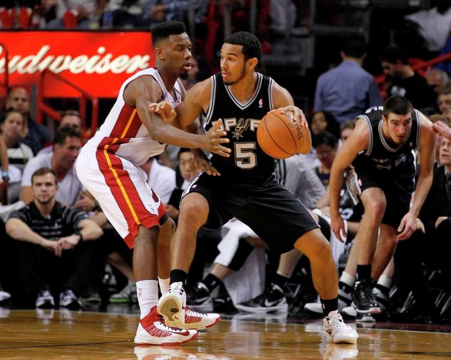 The Spurs' Cory Joseph (5) drives as the Heat's Norris Cole (30) defends  Thursday, Nov. 29, 2012,  in Miami. Photo: Alan Diaz, Associated Press / AP