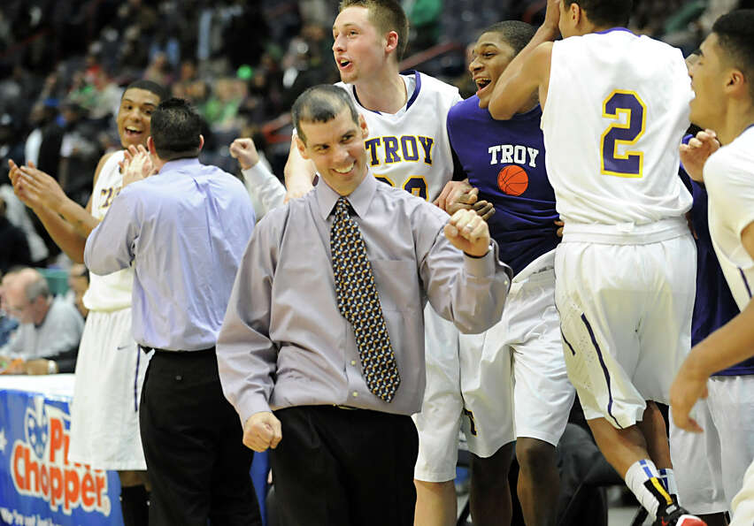 The Troy basketball team and coach Richard Hurley celebrate after the end of the game buzzer goes of
