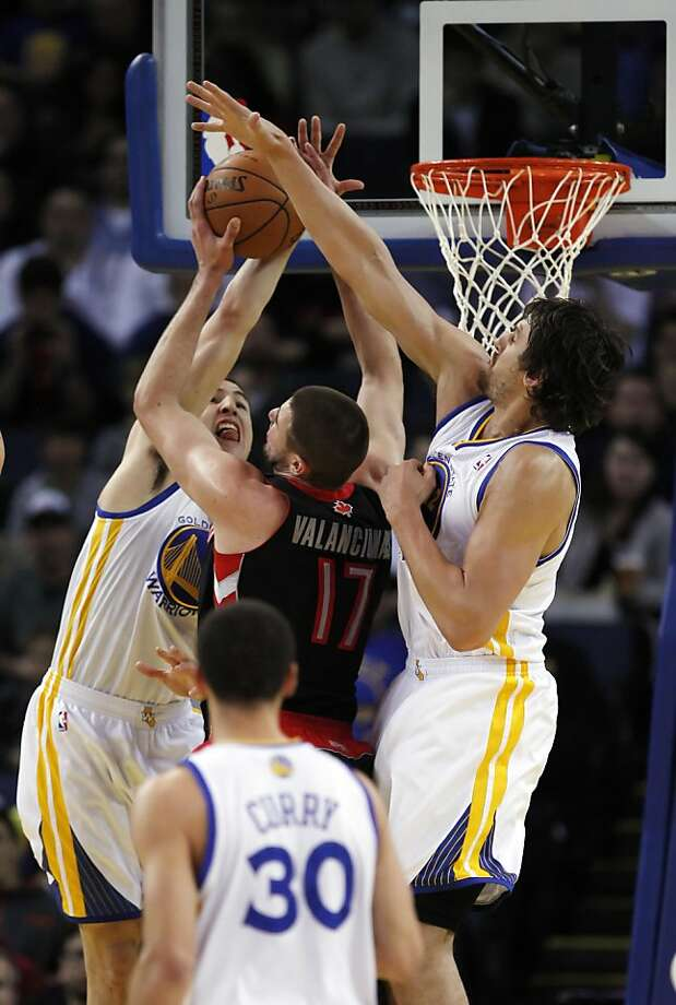 Klay Thompson, left, and Andrew Bogut, right, guard against Toronto's Jonas Valanciunas in the first half. The Golden State Warriors played the Toronto Raptors at Oracle Arena in Oakland, Calif., on Monday, March 4, 2013. Photo: Carlos Avila Gonzalez, The Chronicle