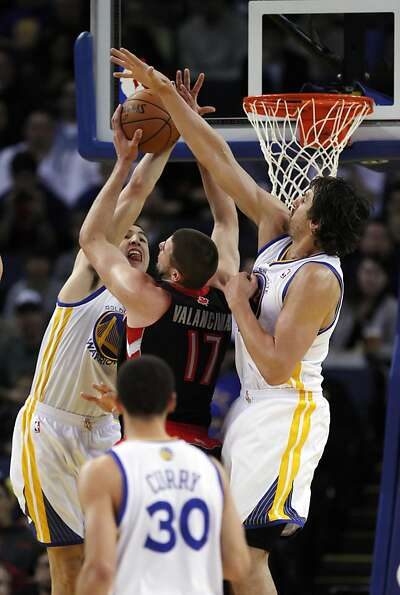 Klay Thompson, left, and Andrew Bogut, right, guard against Toronto's Jonas Valanciunas in the first